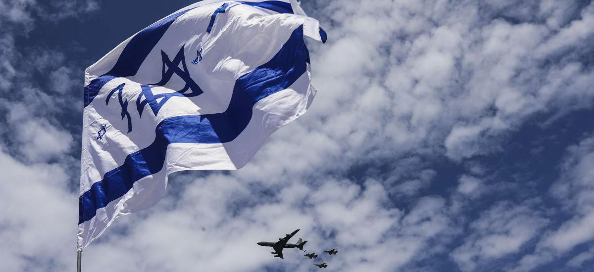 An Israeli flag is seen as Israeli Air Force fighter jets fly over Tel aviv beach during a performance to mark the 71st Independence Day. Photo: Ilia Yefimovich/dpa