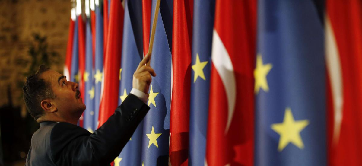 An official adjusts Turkey's and European flags prior to the opening session of a high-level meeting between EU and Turkey, in Istanbul, Thursday, Feb. 28, 2019.