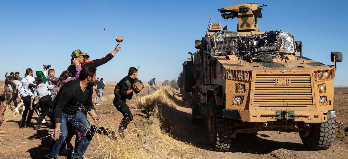 Kurdish demonstrators hurl rocks at a Turkish military vehicle on November 8, 2019, during a joint Turkish-Russian patrol near the town of Al-Muabbadah in the northeastern part of Hassakah on the Syrian border with Turkey.
