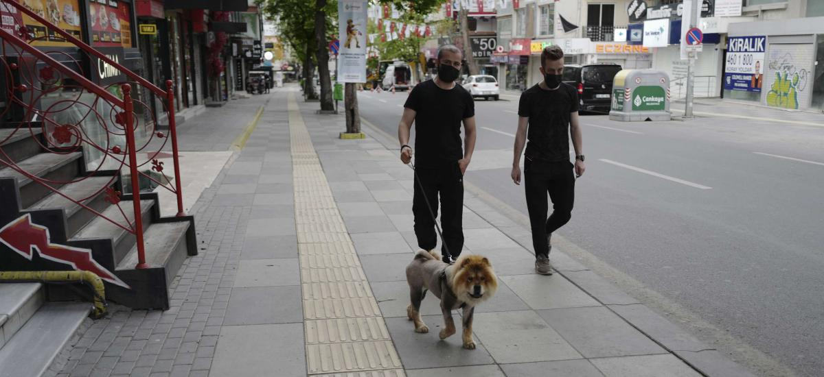 People walk in a nearly deserted street in the city center, in Ankara, Turkey, Sunday, May 2, 2021. Turkish security forces patrolling main streets and set up checkpoints at entry and exits points of cities, to enforce Turkey's strictest COVID-19 lockdown to date. (AP Photo/Burhan Ozbilici)