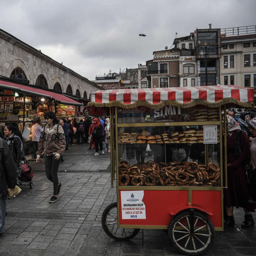 "A street vendor sells traditional Turkish backery ""Simit"" as people shop near the New Mosque area in Istanbul's Eminonu district on November 6, 2018. (AFP)"
