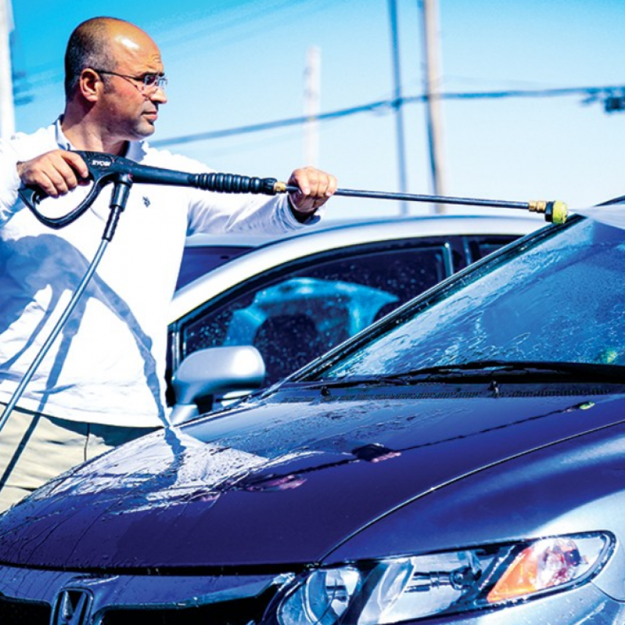 Omer Ozyurt power-washing a car on his dealership's lot. Coulter, for Riverfront Times,