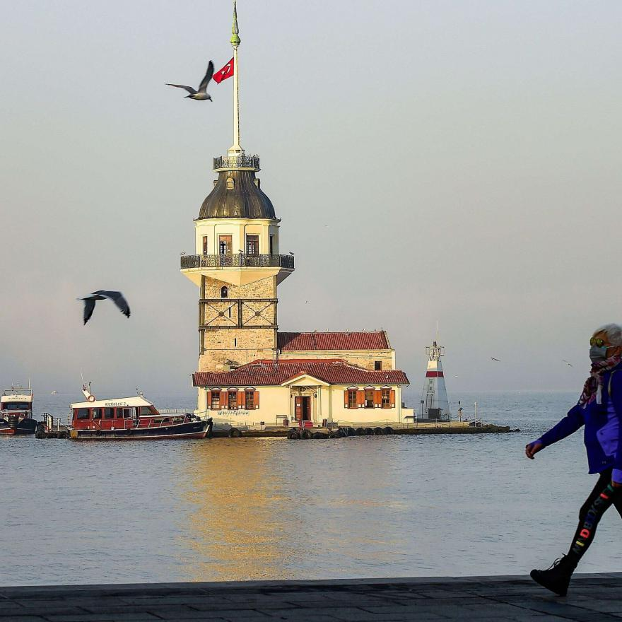 A woman walks past the Maidens Tower on the seaside in the Uskudar district of Istanbul, during a foggy day in Istanbul, on October 25, 2020. (Photo by Yasin AKGUL / AFP)