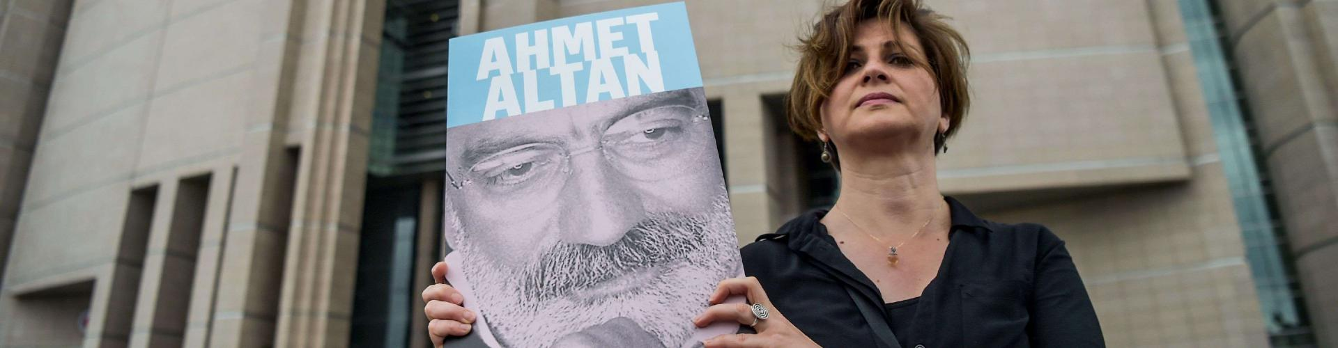 A journalist with a photograph of Ahmet Altan